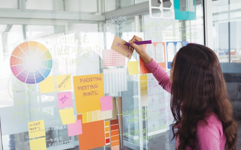 person brainstorming design solutions on a dry erase board
