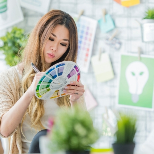 woman choosing brand colors from a color wheel